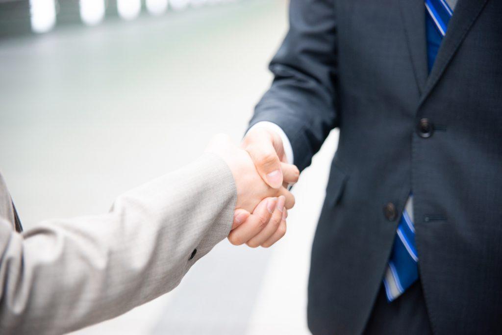 トライアル雇用契約を結び握手する雇用主と従業員