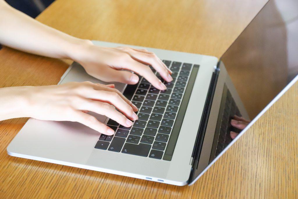 計画書をPCで作成する女性の手